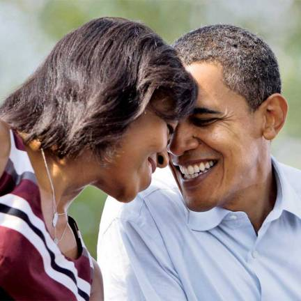 Democratic presidential candidate Sen. Barack Obama, D-Ill., shares a moment with his wife Michelle Obama as Democratic vice presidential candidate Sen. Joe Biden, D-Del., speaks at a rally in front of the Detroit Public Library in Detroit, Mich. Sunday, Sept. 28, 2008.(AP Photo/Alex Brandon)