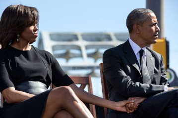 "March 7, 2015 ""I was moving around trying to capture different scenes away from the stage during the event to commemorate the 50th Anniversary of Bloody Sunday and the Selma to Montgomery civil rights marches. When I glanced back towards the stage, I noticed the President and First Lady holding hands as they listened to the remarks of Rep. John Lewis. I managed to squeeze off a couple of frames before they began to applaud, and the moment was gone."" (Official White House Photo by Pete Souza) This official White House photograph is being made available only for publication by news organizations and/or for personal use printing by the subject(s) of the photograph. The photograph may not be manipulated in any way and may not be used in commercial or political materials, advertisements, emails, products, promotions that in any way suggests approval or endorsement of the President, the First Family, or the White House."